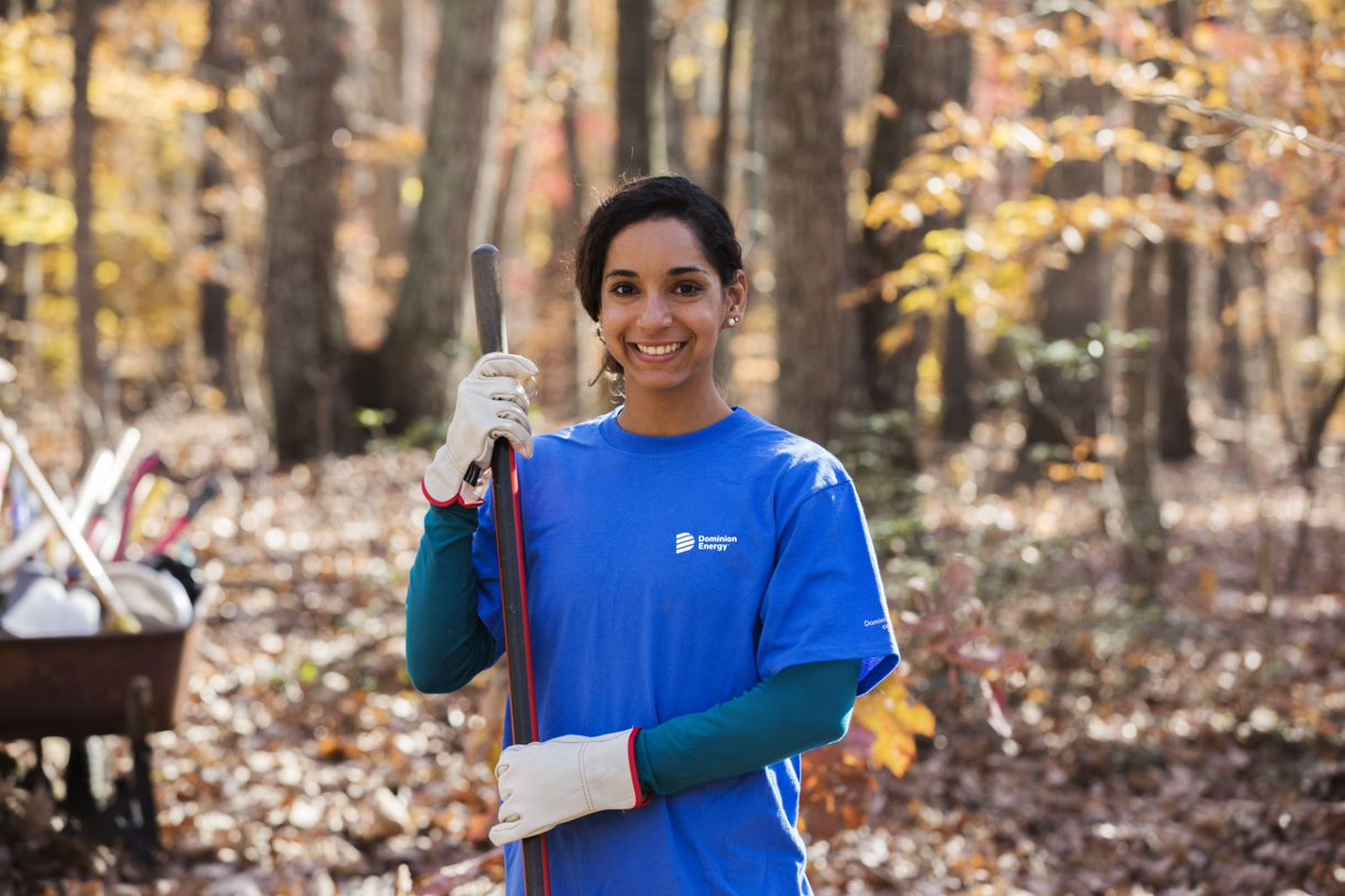 Picture of a Dominion Energy woman employee holding a rake and smiling at the camera.