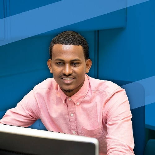 A man looking at his computer, working and smiling