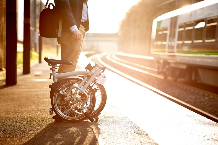 A man with bicycle waiting on a train station platform