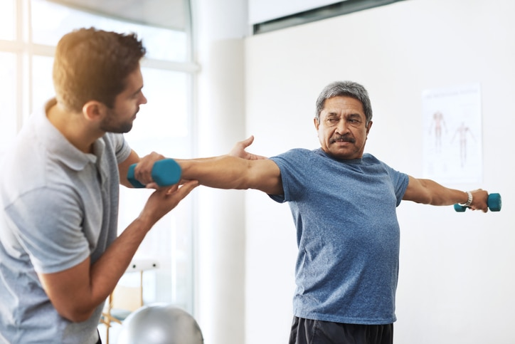A man holding two dumbbells with outstretched arms, assisted by another man