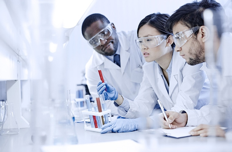 Two men and one woman in the lab with safety glasses