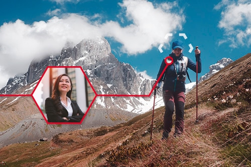 A woman is hiking in the mountains. She can also be seen in a smaller picture in a business environment.