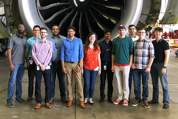 Group of 11 people in Hanger standing in front of Engine prop