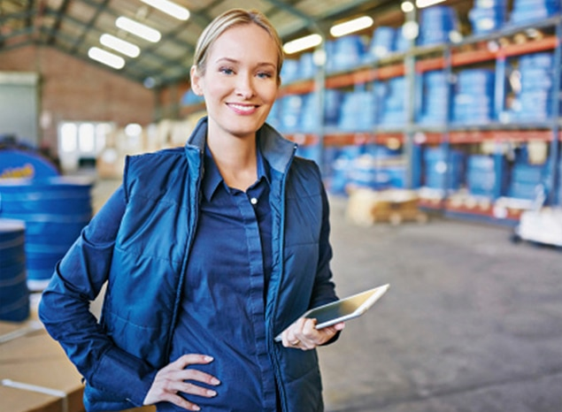 Woman standing in well-organized warehouse.
