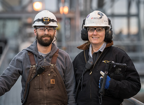 One man and one woman wearing Xcel Energy safety gear smile