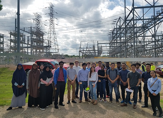 Group of interns at a substation tour posing for a picture