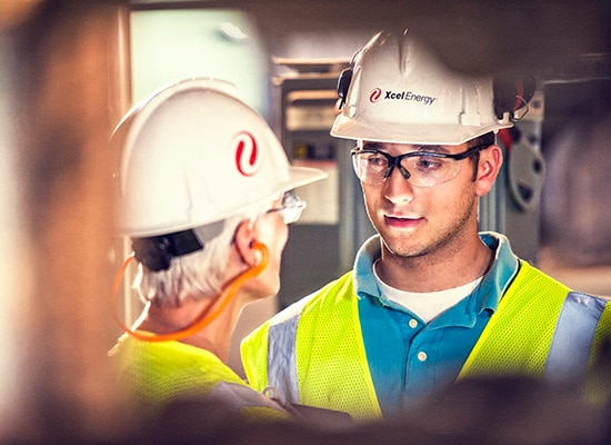 Two Excel Energy workers in safety gear facing each other talking