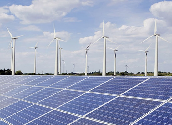 Wind turbines next to solar panels with blue sky