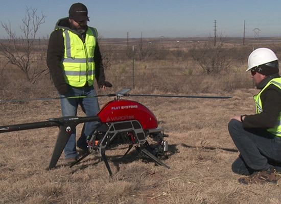Two men wearing safety gear stand next to a drone in an open field