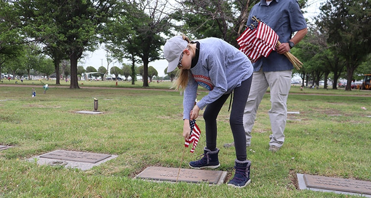 Picture of girl placing American flag at a cemetery grave stone