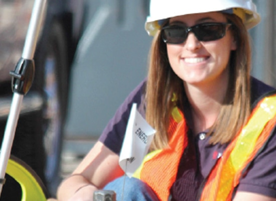 Woman in Xcel Energy hard hat, safety vest, and sunglasses smiles at camera