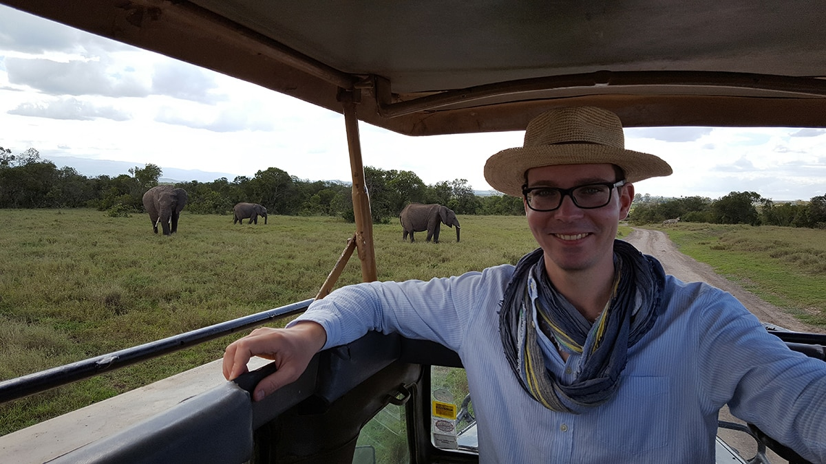 man in hat rides vehicle on safari