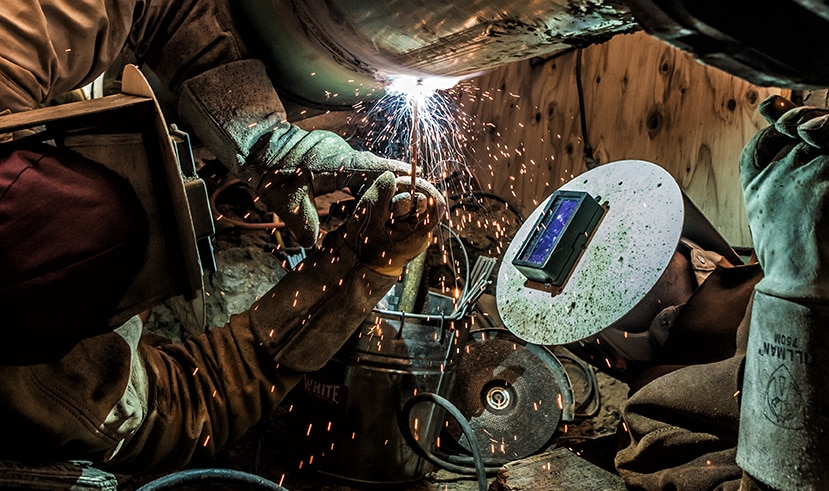 Two welders working on a pipeline weld