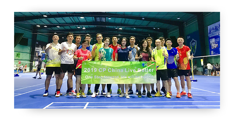 Employees in China standing in a badminton court holding the CP China Live Better program banner