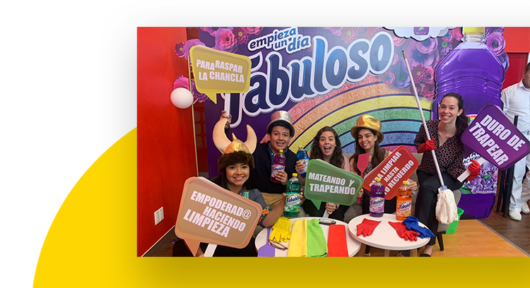 Employees holding signs with Spanish phrases in front a rainbow colored Fabuloso banner.