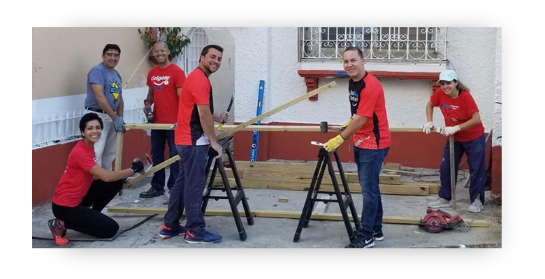 Group of employee volunteers wearing red Colgate shirts with saw horses and tools standing in front of a building
