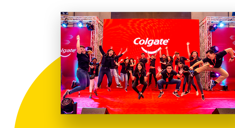 Group of employees jumping and dancing at an annual celebration in front of a red Colgate banner