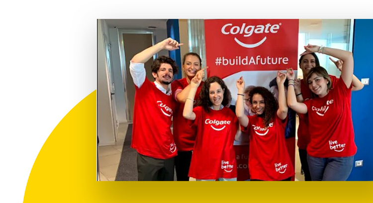 A group of employees wearing red Colgate Live better t-shirts smiling and pointing at a buildAfuture banner