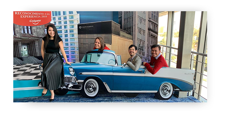1 employees standing in front of a blue convertible automobile model with 3 other employees sitting in it