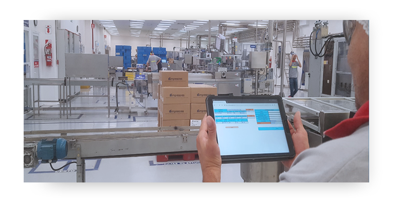 Hands holding an electronic tablet with images on the screen with factory production lines and boxes in the background