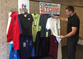 employee at company store looking at shirts