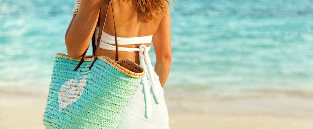 Woman at beach carrying straw bag with heart icon