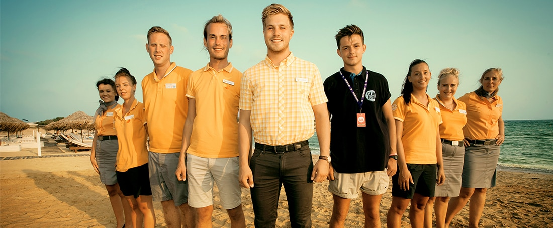 Thomas Cook staff in uniform standing on beach at sunset