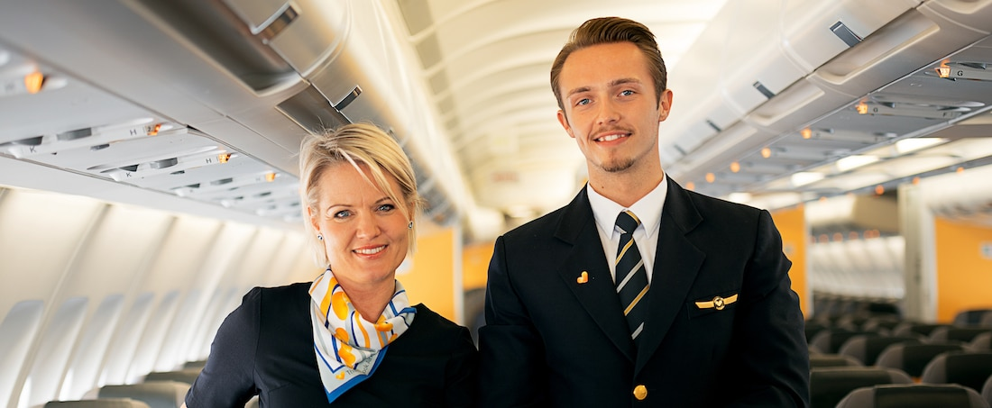 Female and male flight crew in Thomas Cook uniforms in airplane