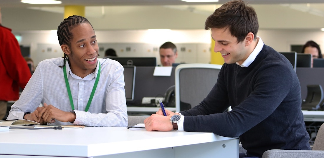 Two young male workers at a desk