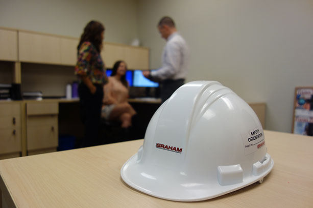 Picture of a hard hat and Graham employees working in the background.