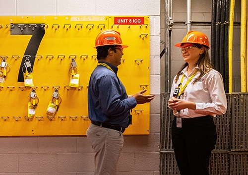 A female supervisor speaks consults another employee in a hallway.